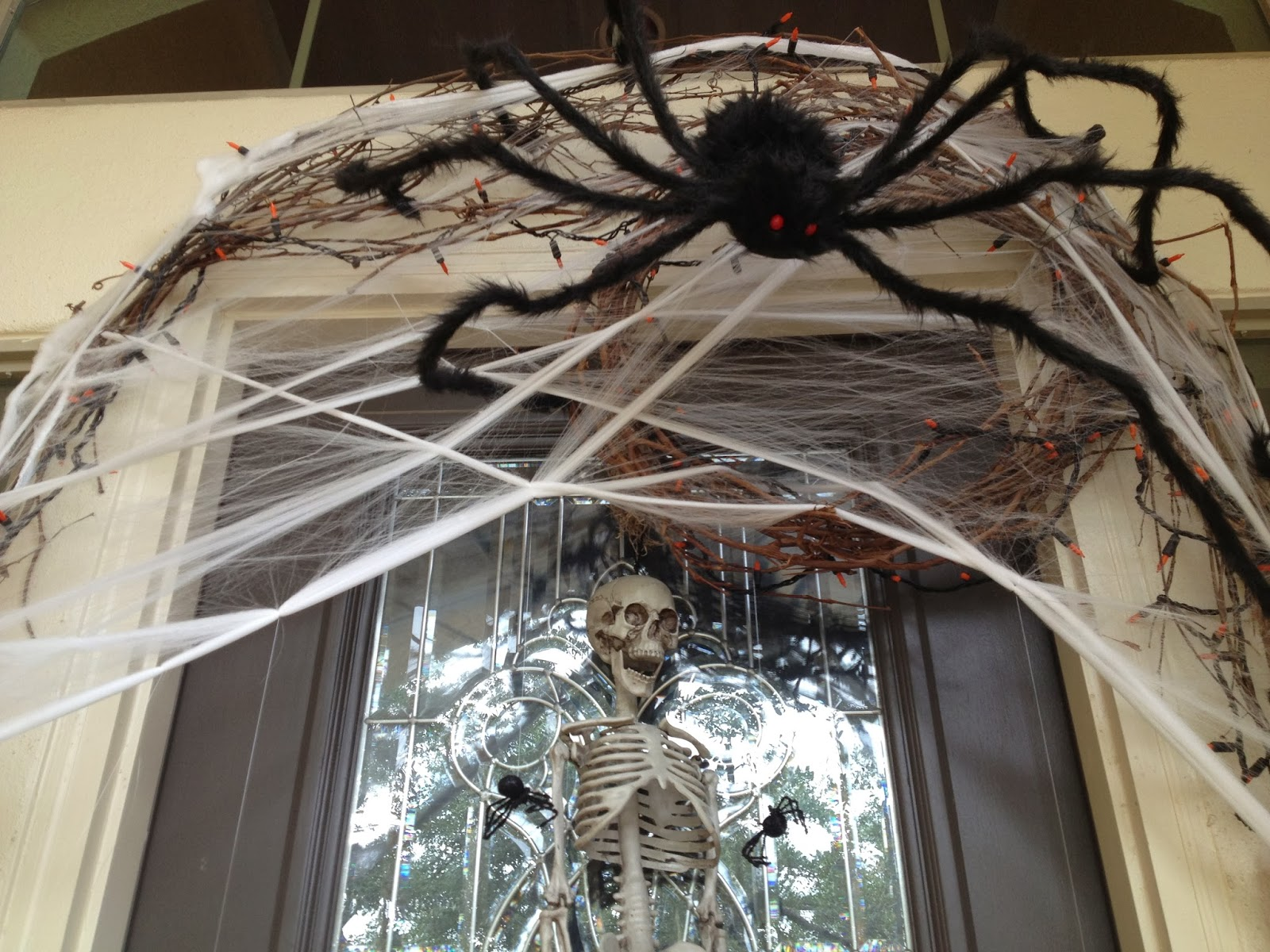 decorations-spooky-spider-web-and-skull-in-glass-frame-front-door-as-marvelous-outdoor-halloween-decoration-ideas-attractive-outside-halloween-decorating-ideas